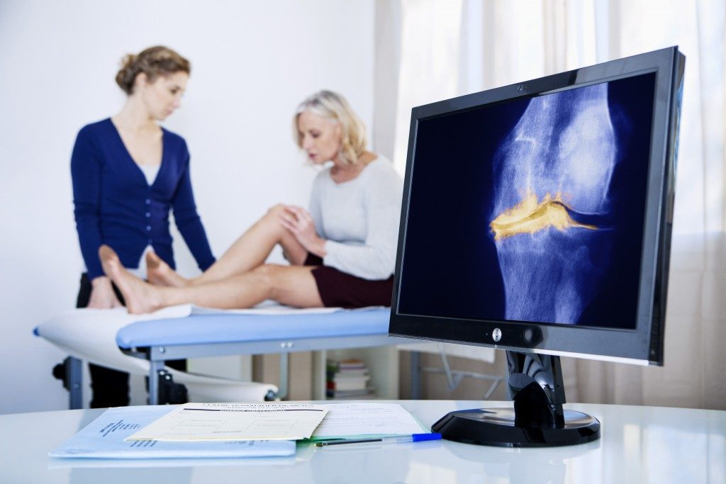 woman experiencing knee pain and getting treatment
