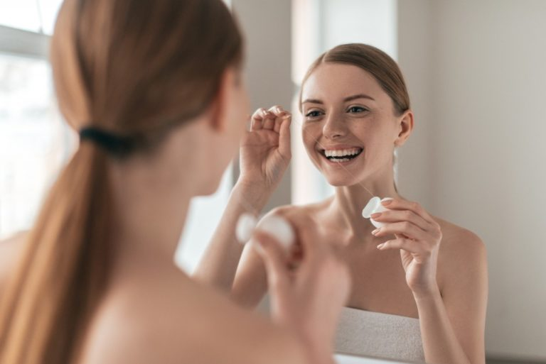 Woman cleaning her face while looking at the mirror