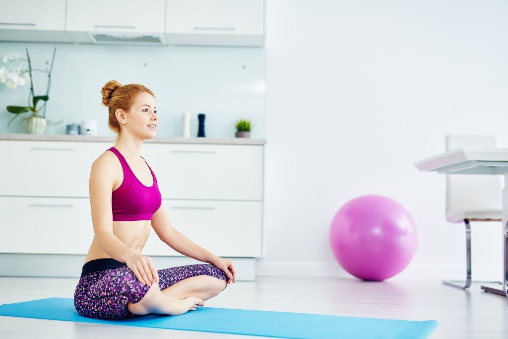 red haired woman doing yoga exercises at home on floor