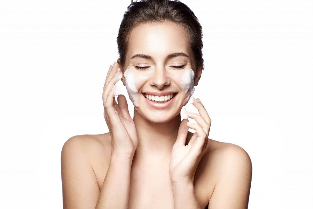 Woman cleansing her face with a white background