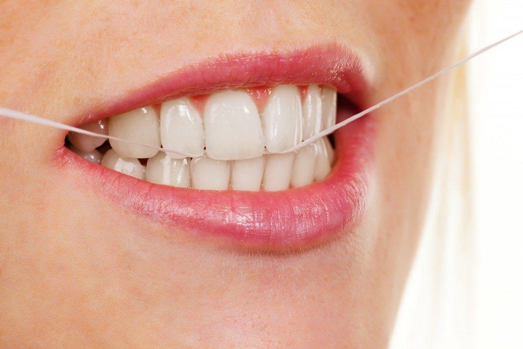 girl using dental floss