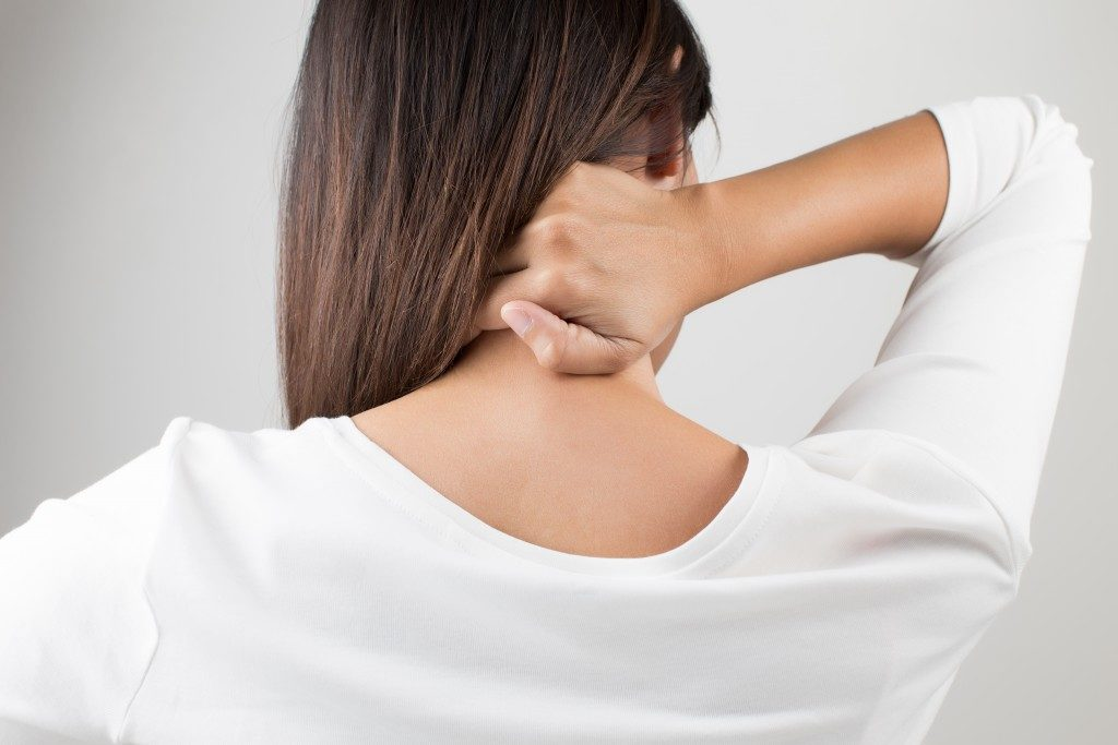 woman having pain in the back and neck