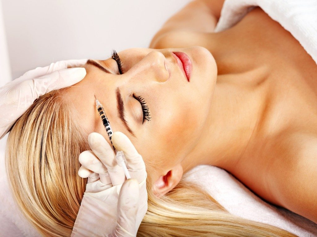 woman giving botox injections