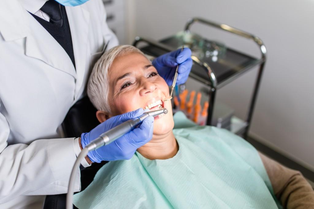 elderly woman getting teeth cleaned