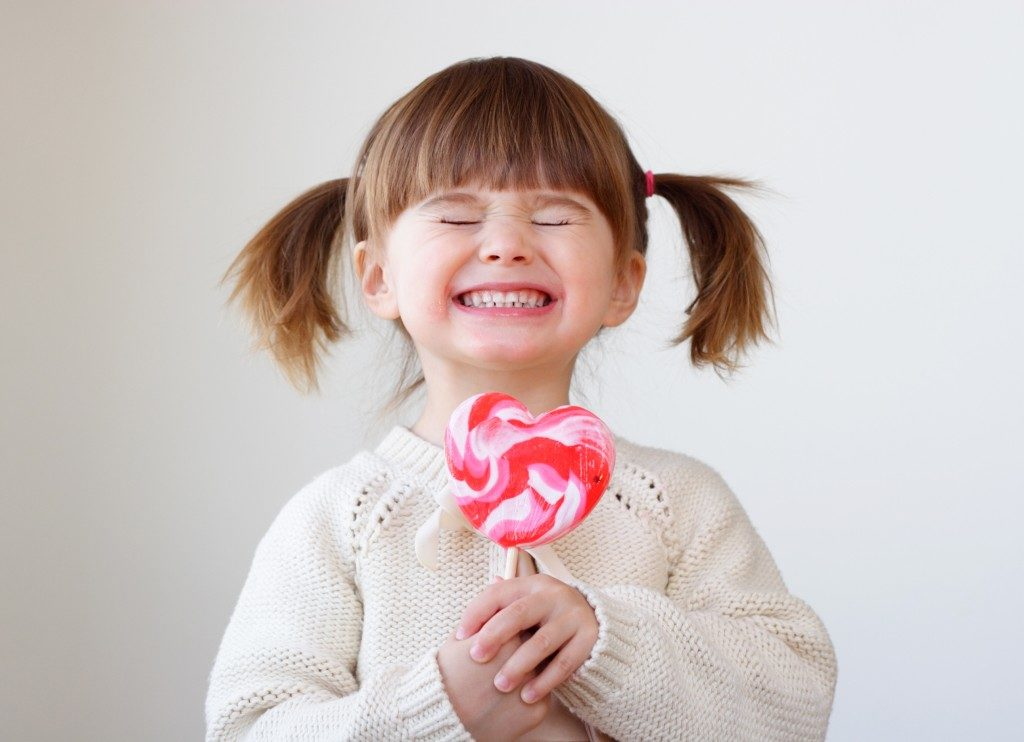 ittle girl holding a big heart-shaped lollipop