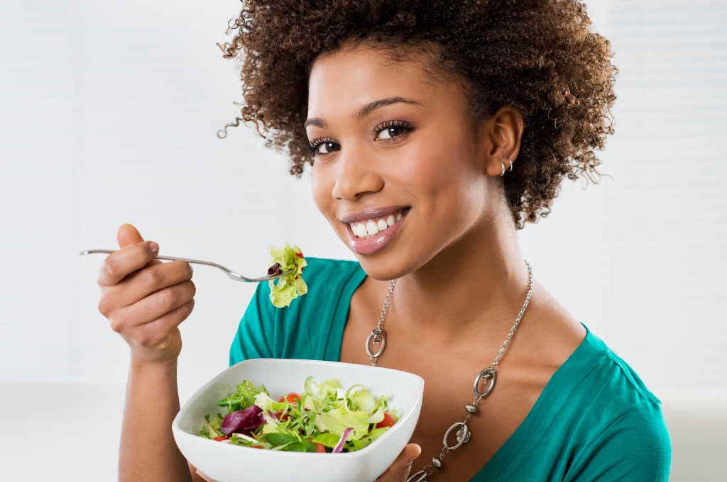 woman smiling with a salad