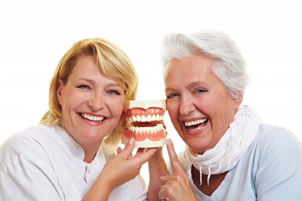 senior citizen being shown model of teeth
