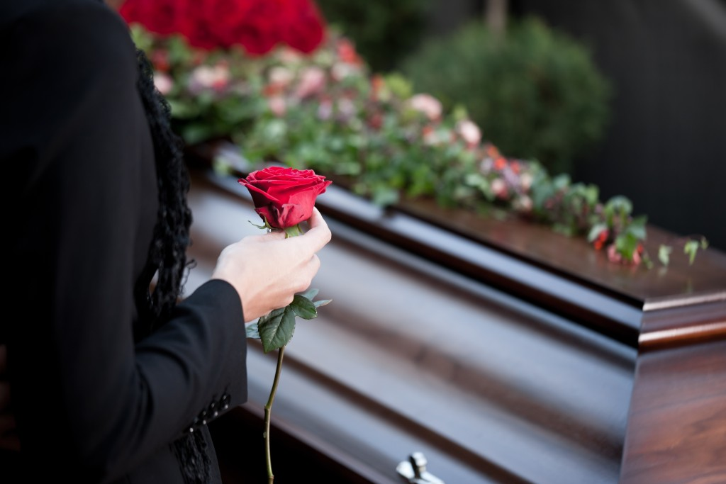 Woman carrying a rose to place above the coffin