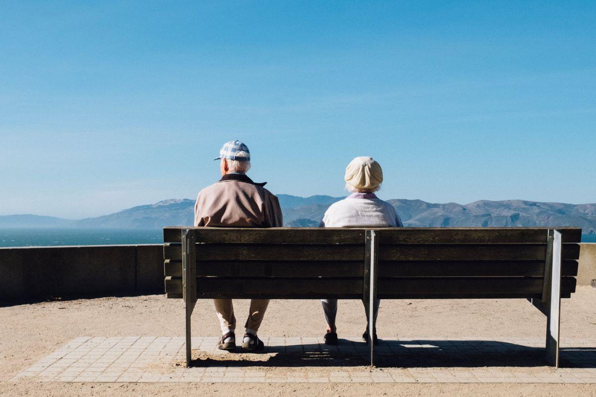 elder couple sitting at park bench