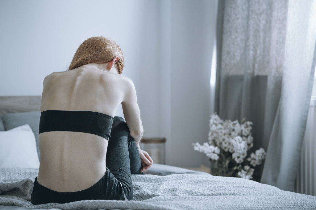 depressed woman sitting on her bed
